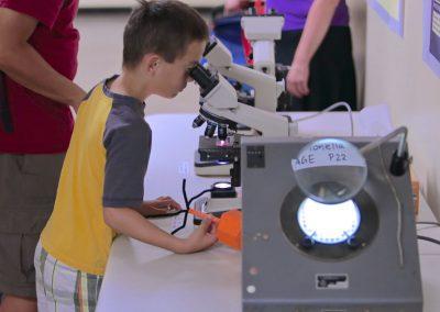 kid looking into microscope.