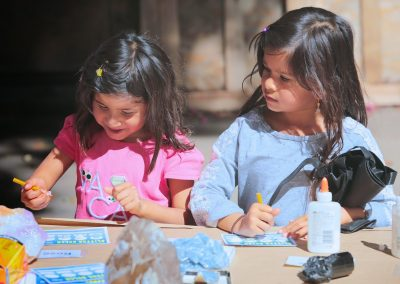 two kids writing their names on Glitter Gulch card with minerals glued on that they found.