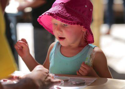 kid looking at rocks samples looking amazed.