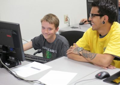 kid using computer smiles seated next to student.