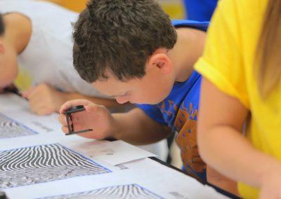 kid looking at fingerprint with magnifying loop.