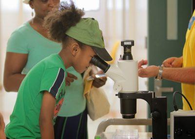 kid looks into microscope.