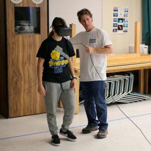 Professor demonstrating virtual reality to student wearing googles.