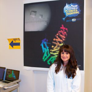 Student standing in front of large poster with crystals and structures magnified.