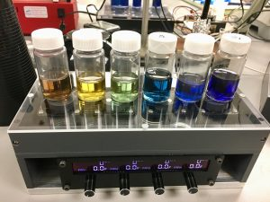 6 test tubes with different colored liquids in device