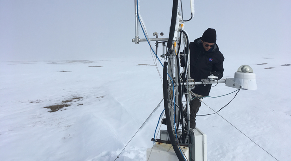 Kyle Arndt checking on the measurement equipment in the snow.
