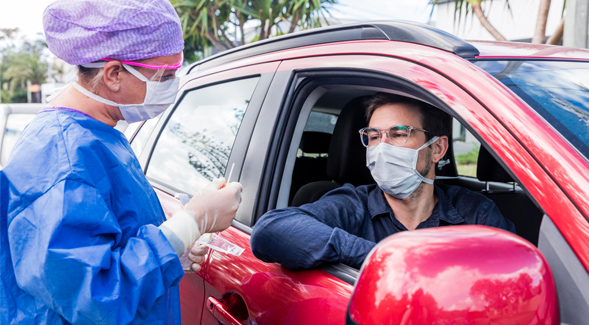 outside, a medical worker is about to swab a patient's nasal cavity.