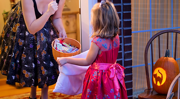 little girl in dress standing at door holding bag with adult handing her candy.