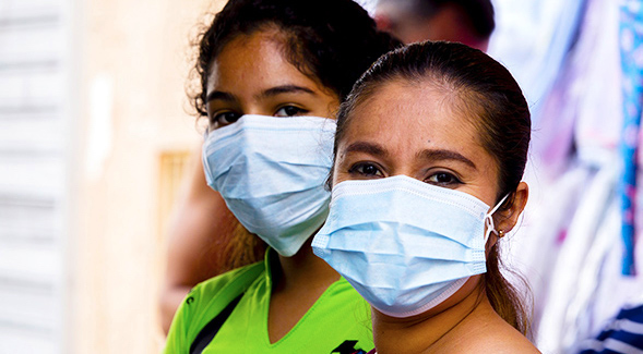close-up of latinas wearing thin light blue masks over mouth and nose