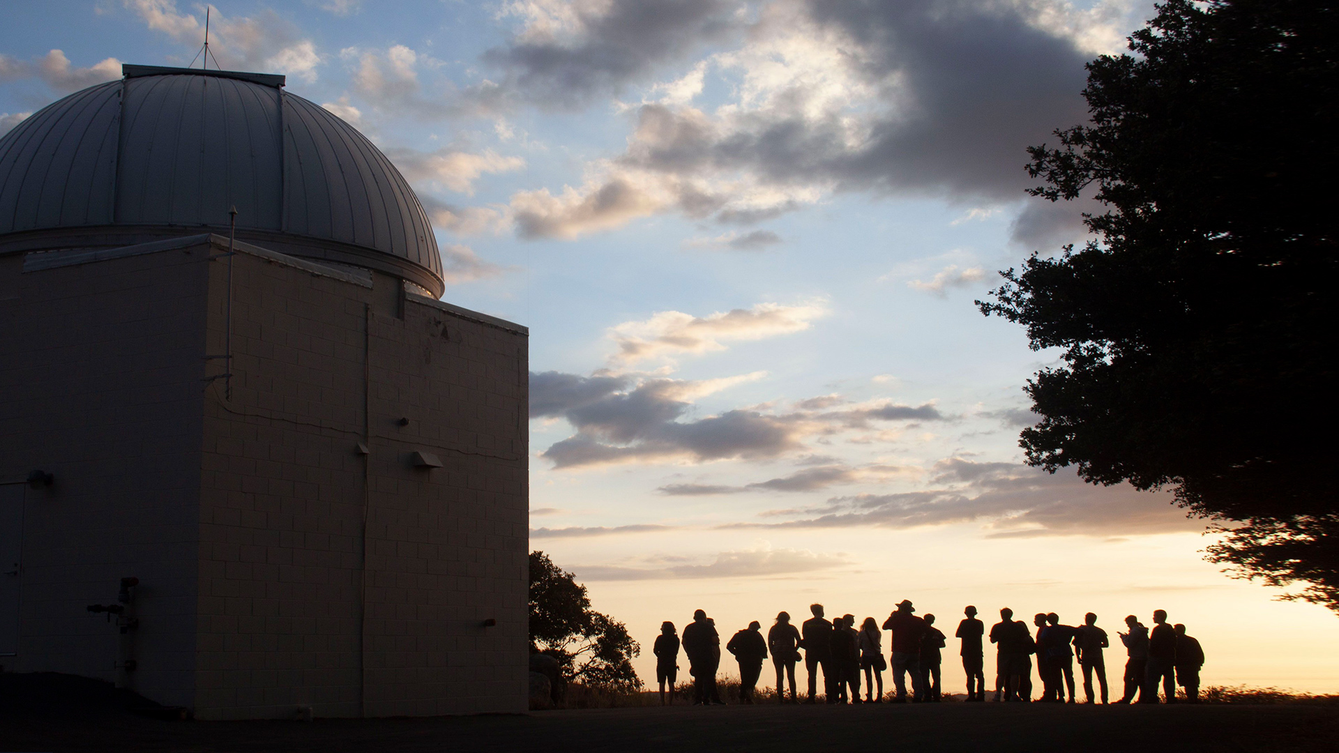 At sunset on top of Mt. Laguna Observatory, the silhouettes of 20 people standing next to a telescope dome structure outside.