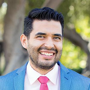 Headshot of Rodrigo Navarro Perez in suit, outside.