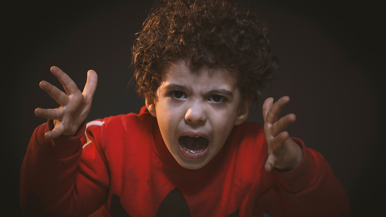 Close-up of young angry boy facing us with curly hair and red sweatshirt gesturing with hands.