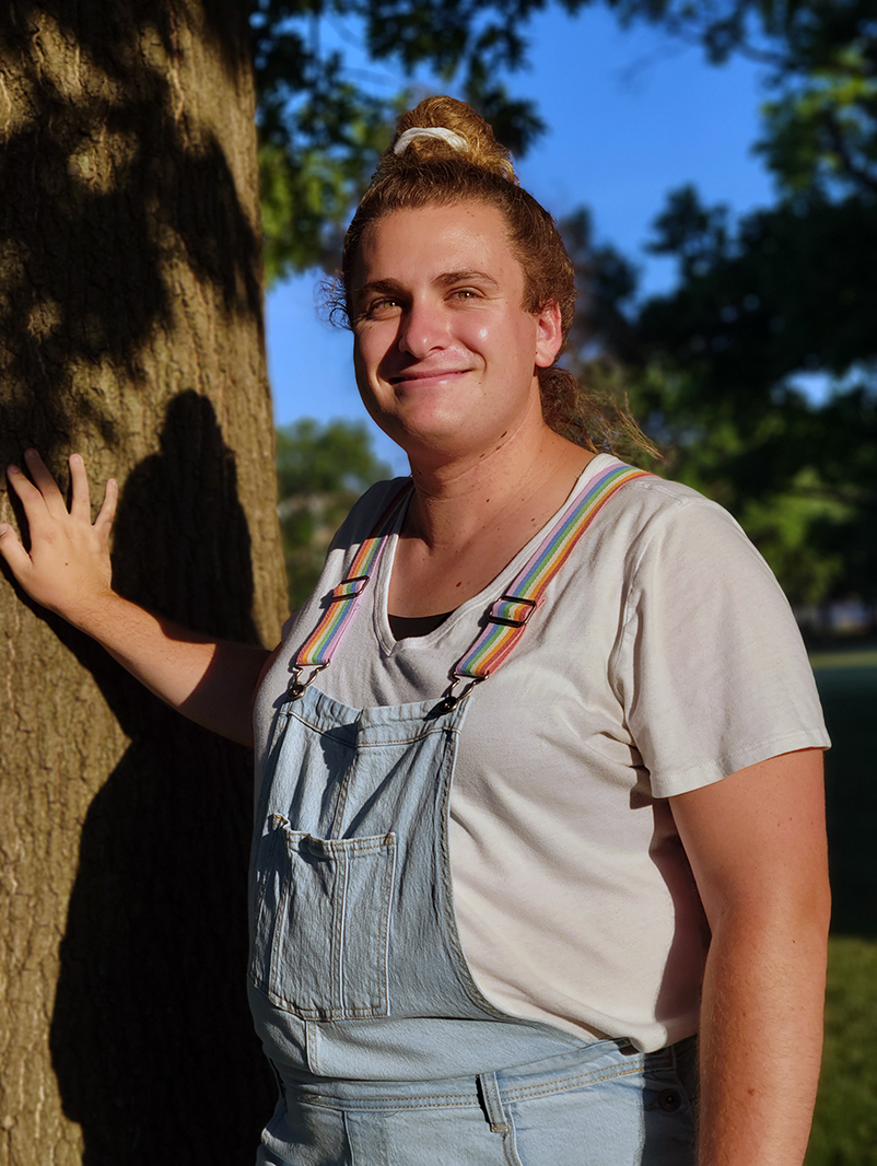 Brienne Hayes wearing pride suspenders poses with hand resting on tree.